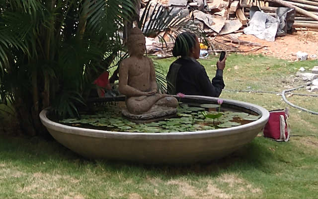Statue of Buddha with a female worker using a mobile phone